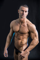 Handsome shirtless bodybuilder in underwear in studio