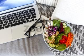 Salad bowl and laptop on sofa