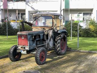 alter Traktor geparkt auf einem Privatparkplatz
