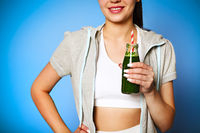 Delighted female with green smoothie laughing against wall background