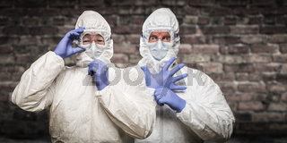 Chinese and Caucasian Men Wearing Hazmat Suit, Goggles and Mask with Brick Wall Background