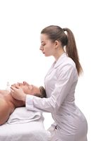 Woman doing massage on face of male client