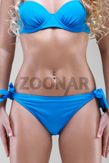 slim model in blue bikini, studio shot
