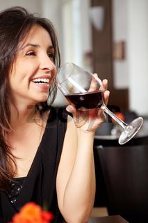 Frau mit Glas Rotwein lacht