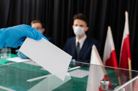 A teenager throws a completed electoral card into the transparent ballot box.