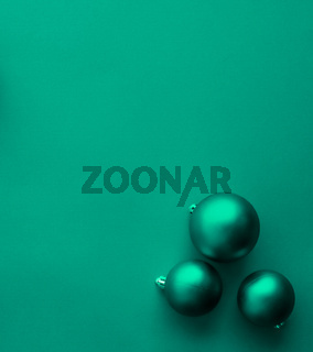 Christmas baubles on green flatlay backdrop, luxury winter holiday card background
