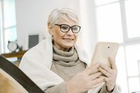 Elderly Grey-haired Woman Is Reading Something Pleasant On Her Tablet And Smiling
