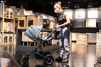 Young mom with newborn in stroller shopping at retail furniture and home accessories store wearing protective medical face mask to prevent spreading of corona virus. New normal during covid epidemic
