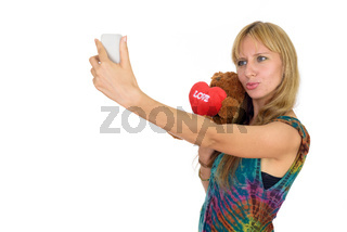 Portrait of beautiful blonde woman taking selfie ready for Valentine's day