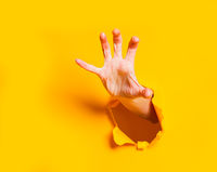 Female hand reaching through torn yellow paper sheet. Seasonal sale, shopping.