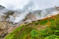 Thrilling view of volcanic landscape, aggressive hot spring, erupting fumarole, gas-steam activity in crater of active volcano