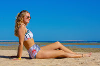 Pretty young dutch woman sits on beach