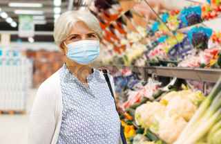 senior woman in medical mask at supermarket