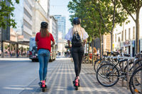 Rear view of trendy fashinable teenager girls riding public rental electric scooters in urban city environment. New eco-friendly modern public city transport in Ljubljana, Slovenia