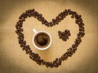 Fresh black coffee and beans creating a heart shape