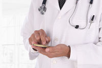 Closeup of a doctor texting on his cell phone in a modern medical facility. Man is unrecognizable.