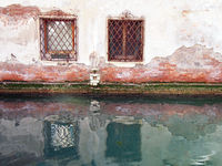 two ornate windows with rusting iron bars in an ancient white plastered brick wall reflected in the still green water of a canal in venice italy