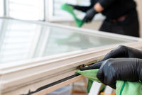 facility management cleaners cleaning a window and window frame with green micro fiber cloths