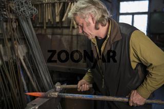 Schmied arbeitet am Amboß