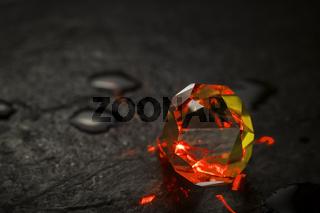 Red illuminated crystal on rainy slate