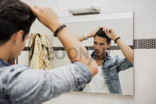 Reflection of Man Bushing Hair in Mirror