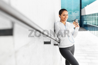 african american woman with earphones and phone
