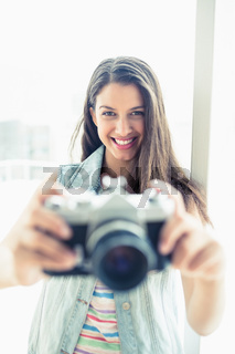 Smiling young woman taking a photo at camera
