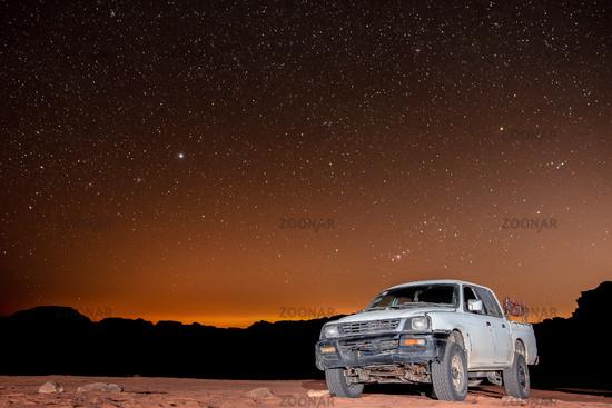 Clear night sky with stars above truck in Wadi Rum desert in Jordan