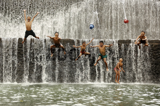 Boys have fan on the artificial waterfall on Unda River and enjoy swimming at the dam ,Bali