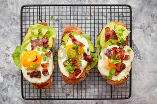 Tasty delicious homemade toasts with fried egg, bacon, avocado, lettuce and chive. Served on grill