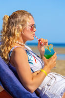 Young woman drinking cocktail on beach