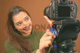 Young beautiful Indian woman vlogging against brown background