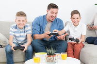 Happy young family playing videogame On TV.