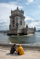 Tourist girls sitting in front of the Belem Tower  at Tagus River, in Lisbon  Portugal