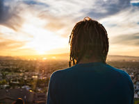 Unrecognizable man with dreadlocks admiring nature during sunset