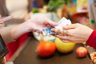 Hände übergeben Euroscheine an Kasse