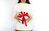 Girl in white sweater holding round present box tied with bright red ribbon during holiday celebration