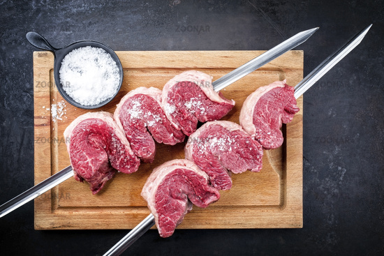 Raw dry aged wagyu picanha barbecue skewer from the cap of rump beef sliced and with salt offered as top view on a wooden rustic cutting board