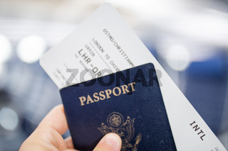 Male hand holding American passport and airplane ticket