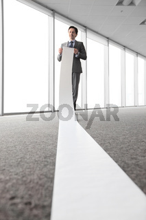 Man reading a long paper