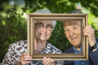 Retired couple hold a frame frame