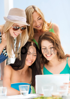 smiling girls looking at tablet pc in cafe