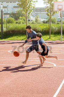Dad and son playing basketball barefoot on a playground