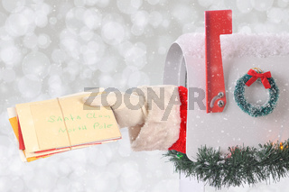 Santa Claus arm holding a stack of Christmas letters coming out of a mail box with silver bokeh background and snow effect.