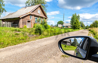 Village wooden houses and reflection in the rearview mirror of a car. Selective focus