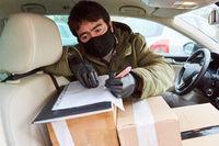Paketbote prüft Lieferung im Innenraum seines Fahrzeugs
