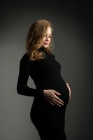 Pregnant woman in black dress in studio