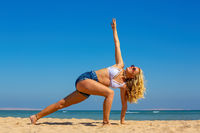 Young woman exercising yoga posture on Egyptian beach