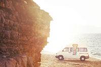 Caravan parked on beach at sunset.