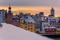 The skyline of the old town of Regensburg on the danube river on cold winter morning in December with fresh snow on the roofs